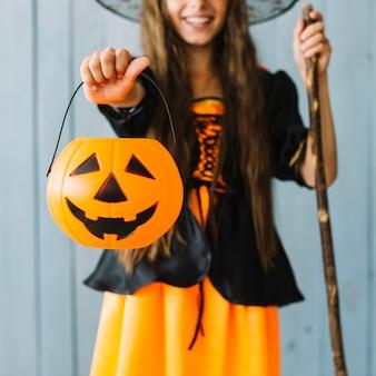 Garota em traje de halloween segurando a cesta na mão