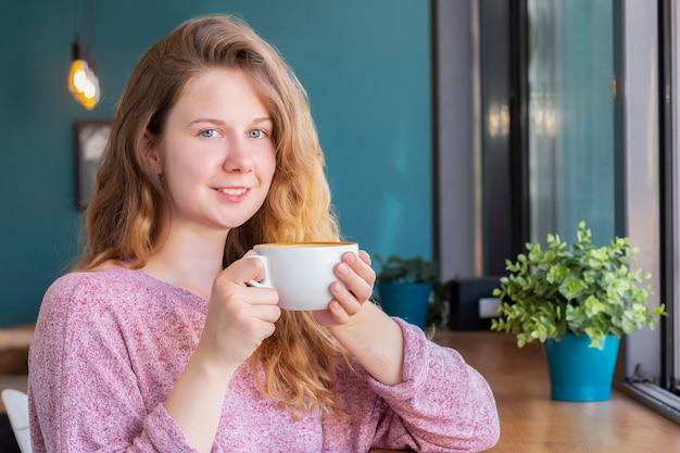 Garota em um café com uma xícara de café, sorrindo e bebendo um café com leite.