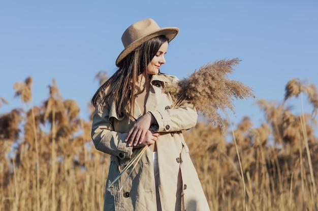 Garota em um campo de junco segurando um buquê de juncos
