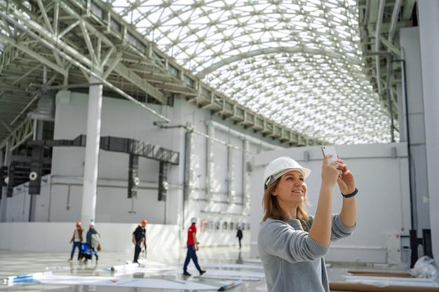 Garota em um capacete com um telefone tira fotos
