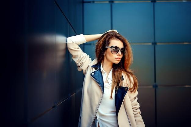 Garota em um casaco bege e jeans azul