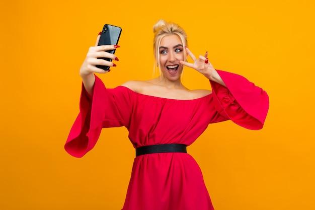 Garota em um elegante vestido vermelho faz uma foto de si mesma no telefone em uma superfície de estúdio amarelo