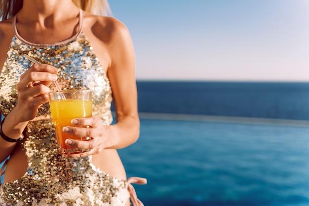 Garota em um maiô caro com um coquetel nas mãos passa as férias perto da piscina do resort