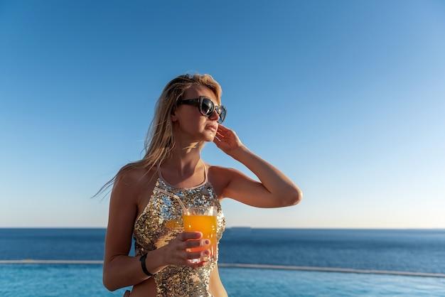 Garota em um maiô caro com um coquetel nas mãos passa as férias perto da piscina no resort