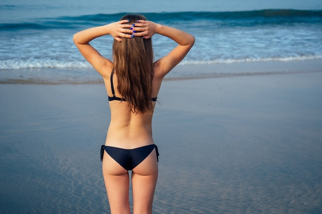 Garota em um maiô preto, tomando banho de sol em pé à beira-mar.