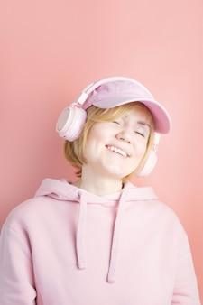 Garota em um moletom rosa e com fones de ouvido rosa em um fundo semelhante em tom