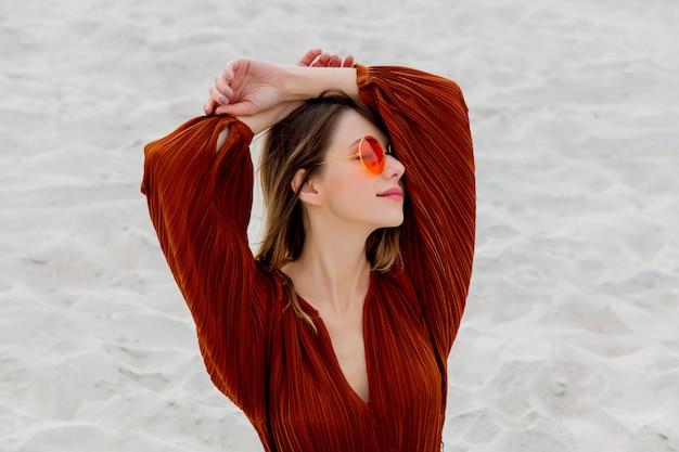 Garota em um óculos escuros e blusa cor de vinho em uma areia branca