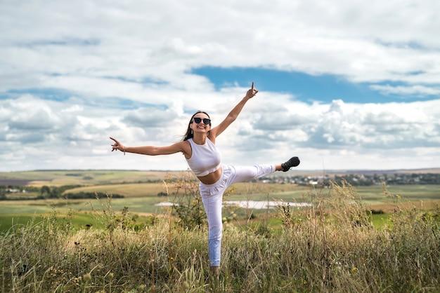 Garota em um pano casual em um campo verde rural vai no verão. estilo de vida