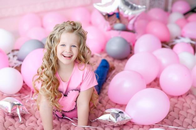 Garota em um quarto rosa e roupas cor de rosa em um fundo de balões