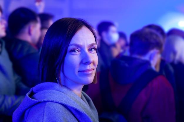 Garota em um show no fundo da multidão de pessoas e luz de néon