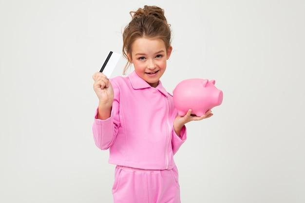 Garota em um terno rosa, segurando um cofrinho e um cartão de crédito em uma parede branca
