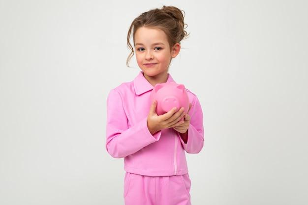Garota em um terno rosa, segurando um pote de dinheiro em uma parede branca com espaço em branco