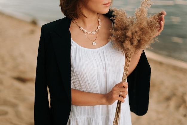 Garota em um vestido branco e jaqueta preta com um buquê na praia. verão