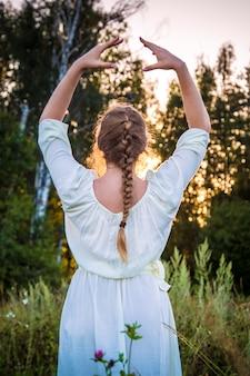 Garota em um vestido branco olha para o pôr do sol na floresta, respira e relaxa. mulher com cabelo trançado