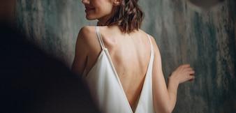 Garota em um vestido branco vira um rosto com um sorriso para um cara