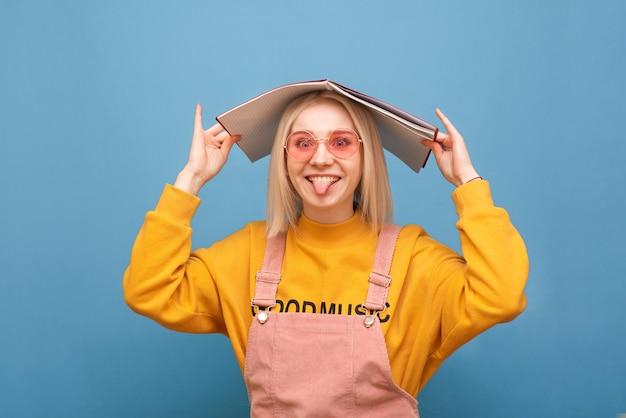 Garota em um vestido casual brilhante e óculos de sol rosa segurando um caderno na cabeça