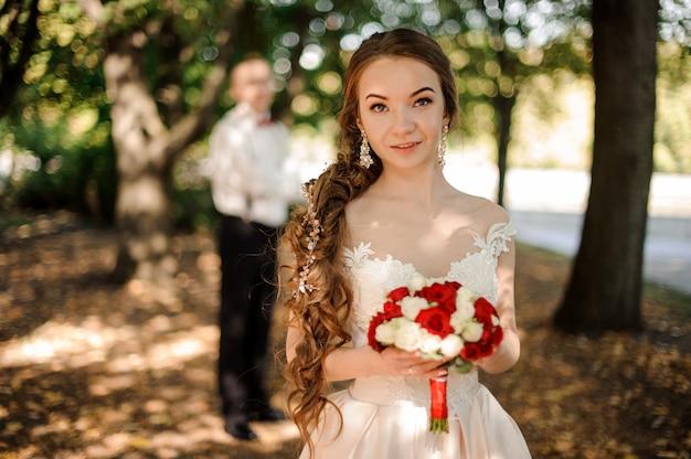 Garota em um vestido de noiva com um buquê de flores