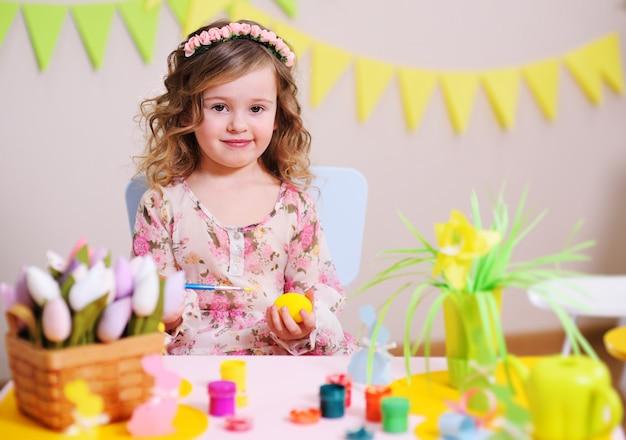 Garota em um vestido inteligente pinta um ovo sentado em uma mesa com uma decoração de páscoa