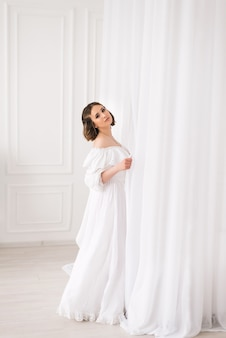 Garota em um vestido longo branco em uma sala iluminada