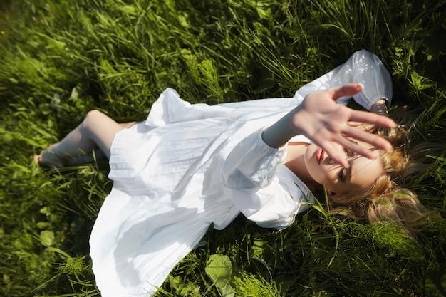Garota em um vestido longo branco encontra-se na grama em um campo. mulher loira ao sol em um vestido leve. garota descansando e sonhando, maquiagem perfeita de verão no rosto