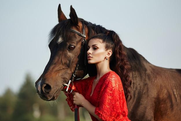 Garota em um vestido longo fica perto de um cavalo, uma linda mulher acaricia um cavalo e segura o freio em um campo no outono