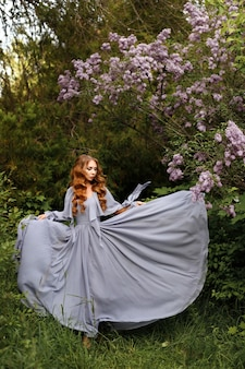 Garota em um vestido longo perto de lilás sobre fundo verde de verão