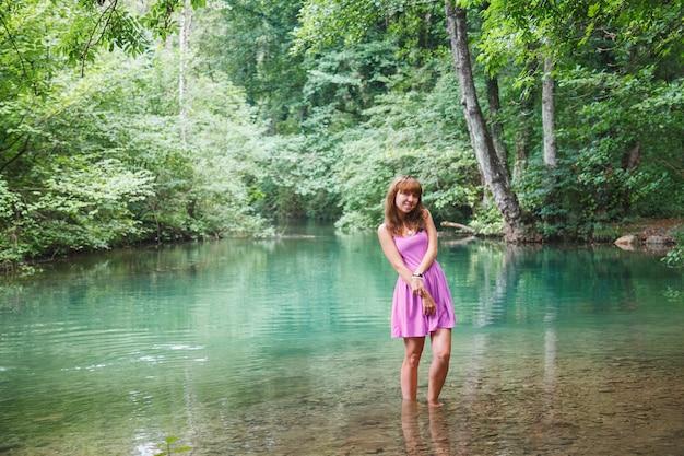 Garota em um vestido rosa curto caminha sobre um rio na floresta