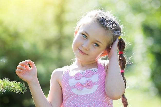 Garota em um vestido rosa na floresta.