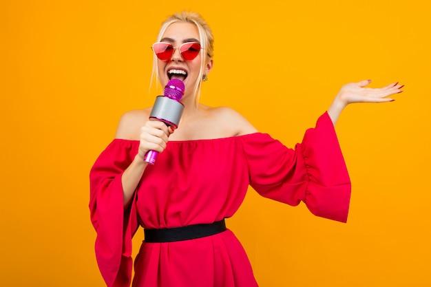 Garota em um vestido vermelho com ombros nus canta com um microfone no estúdio