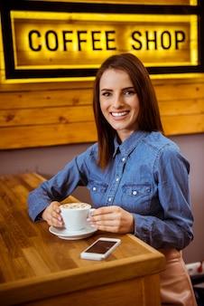 Garota em uma boa casa de café bebe um café delicioso.