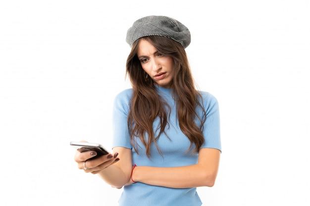 Garota em uma boina com um telefone nas mãos em uma parede branca