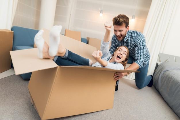 Garota em uma caixa e cara está rolando ela em torno de apartamento
