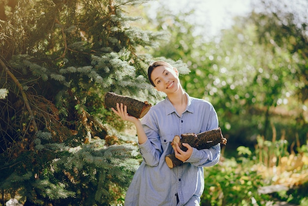 Garota em uma camisa azul em pé nas árvores