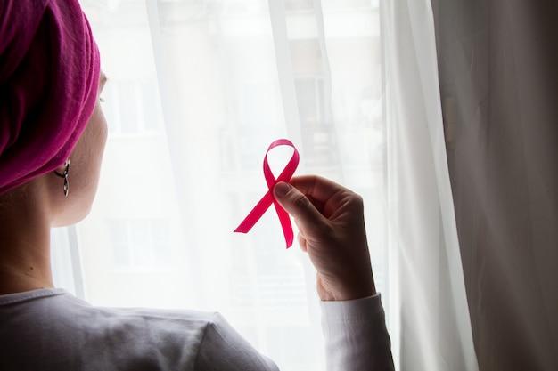 Garota em uma camiseta branca com uma fita rosa nas mãos na frente da janela