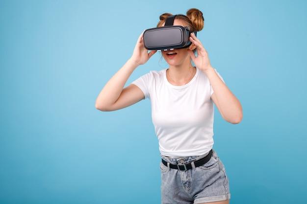 Garota em uma camiseta branca e óculos de realidade virtual no espaço