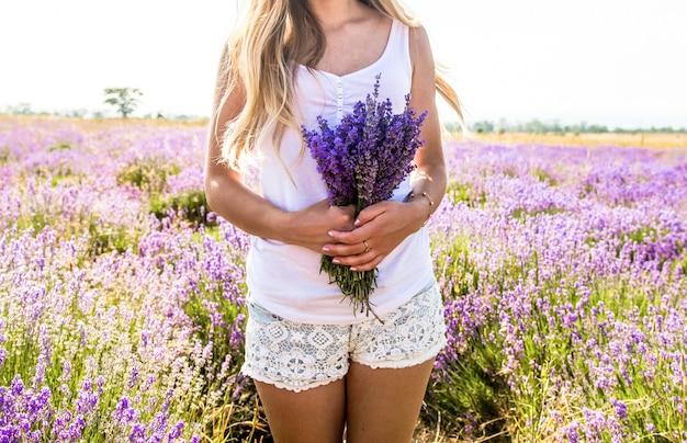 Garota em uma camiseta branca e shorts com um buquê nas mãos fica em um campo de lavanda