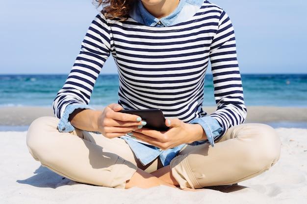 Garota em uma camiseta listrada com um e-book em mãos lendo na praia