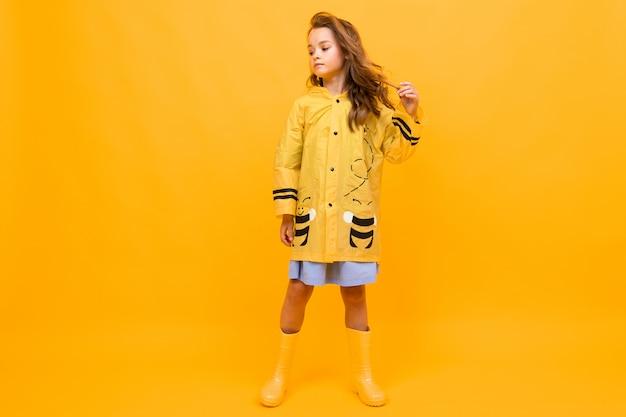 Garota em uma capa de chuva amarela linda sob a forma de uma abelha fica em amarelo com espaço de cópia