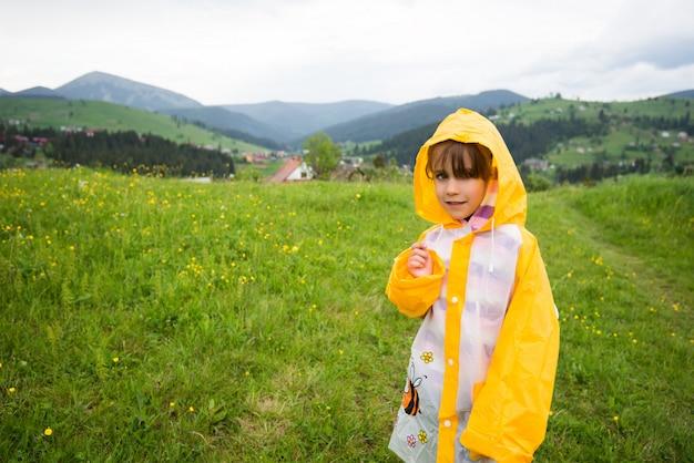 Garota em uma jaqueta amarela caminha ao longo de um campo