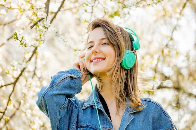 Garota em uma jaqueta jeans e fones de ouvido fica perto de uma árvore de florescência
