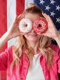 Garota em uma jaqueta rosa sobre fundo vermelho com um donut nas mãos contra um fundo da bandeira americana