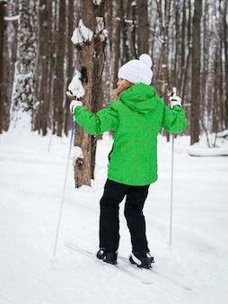 Garota em uma jaqueta verde, esqui na floresta de inverno