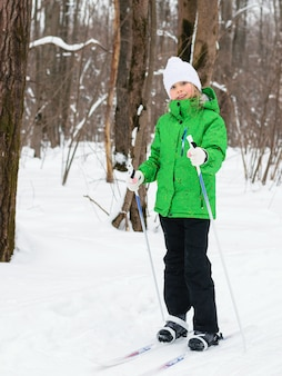 Garota em uma jaqueta verde posando enquanto esquiava na floresta de inverno.