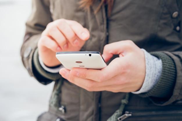 Garota em uma jaqueta verde usa um smartphone enquanto caminhava no fundo do mar