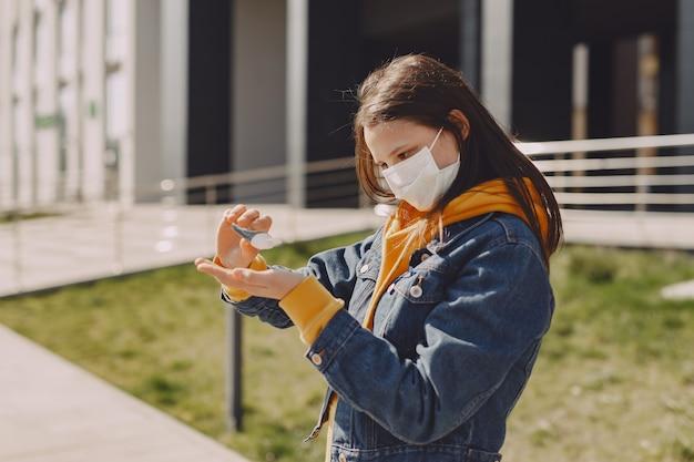 Garota em uma máscara fica na rua