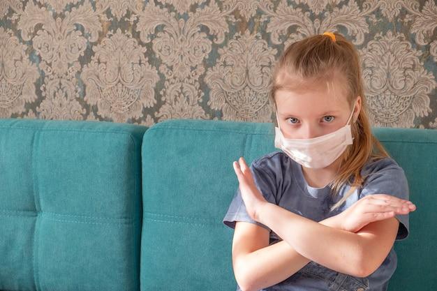 Garota em uma máscara médica com braços cruzados, mostrando o coronavírus de parada
