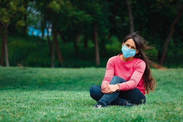 Garota em uma máscara médica na grama