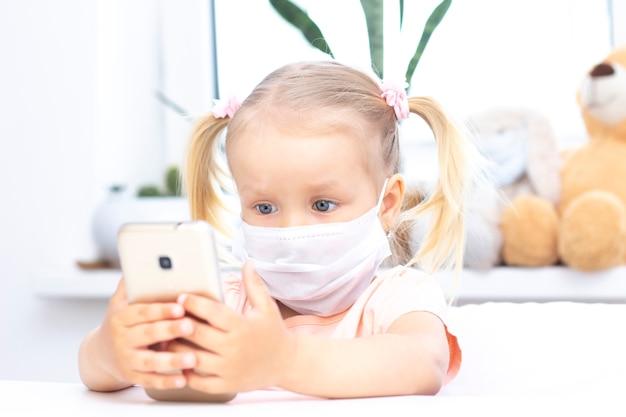 Garota em uma máscara médica protetora usando um telefone celular, um smartphone para videochamadas, conversa com parentes, uma garota senta-se em casa, na webcam do computador on-line, fazendo uma videochamada.