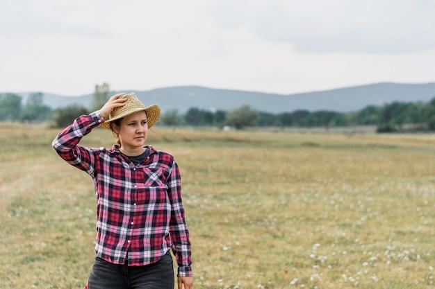Garota em uma merda quadrada vermelha, segurando seu chapéu no campo