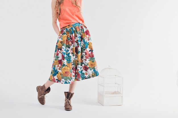 Garota em uma saia colorida e sapatos em branco